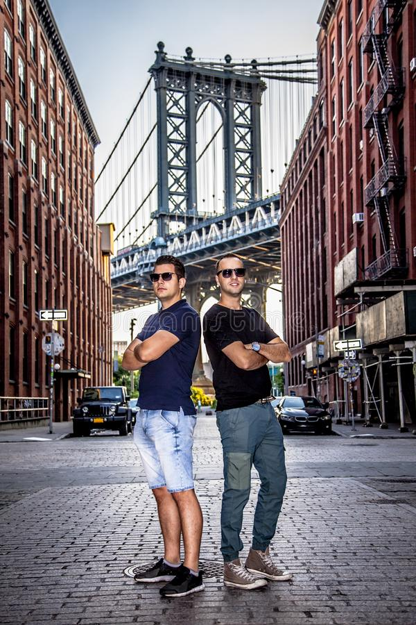 Tourists models enjoying New York City and Dumbo, Brooklyn. Tourists handsome models enjoying and Manhattan Bridge between Manhattan and Brooklyn over East River royalty free stock photos