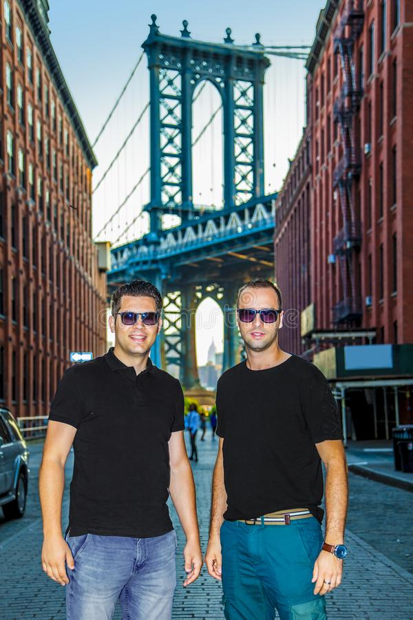 Tourists models posing and enjoying New York City and Dumbo, Brooklyn. Tourists handsome model enjoying and Manhattan Bridge between Manhattan and Brooklyn over royalty free stock images