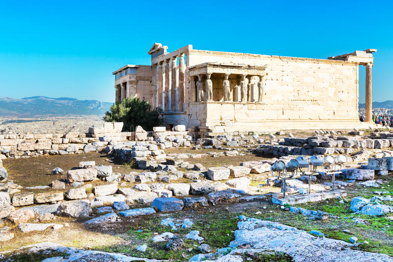 Tourists near Erechtheum temple ruins in Acropolis, Athens. Erechtheum temple ruins decorated with Caryatids female statues in Acropolis royalty free stock image
