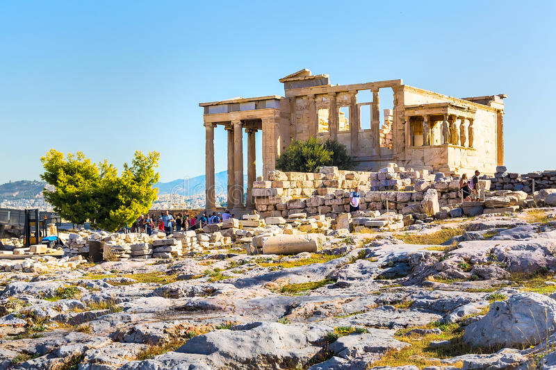 Tourists near Erechtheum temple ruins in Acropolis, Athens. Athens, Greece - October 14, 2016: Tourists near Erechtheum temple ruins decorated with Caryatids royalty free stock image