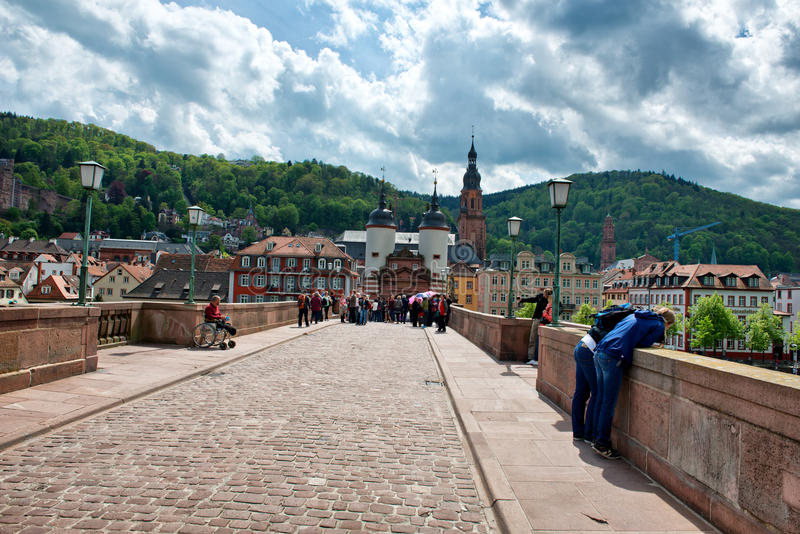 Tourists on Old Bridge to Old Town Heidelberg. Crowd of Tourists on Cobblestone Street of Old Bridge Leading to Old Town Heidelberg in the Lush Green Foothills royalty free stock image