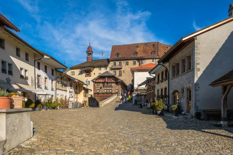 Tourists on the old medieval road in Gruyeres, Switzerland, in autumn light. stock photos