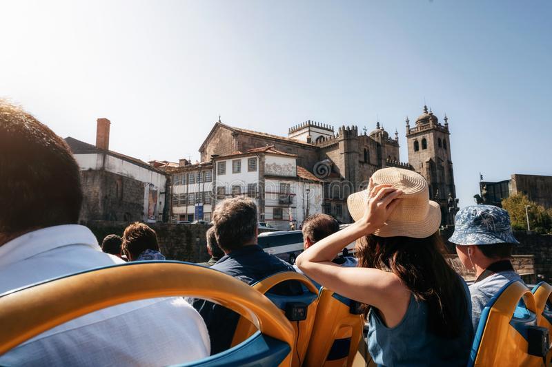 Tourists on open top sightseeing bus in city. Porto, Portugal. Tourists on open top sightseeing bus Hop on hop off in explore city. Cathedral Seu on the royalty free stock photo