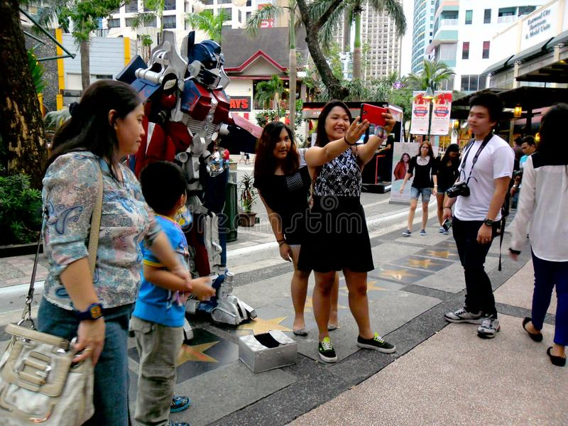 Tourists in a Park in Eastwood City. Tourists take selfies with a mime in a park in eastwood city in libis, quezon city, philippines stock photo