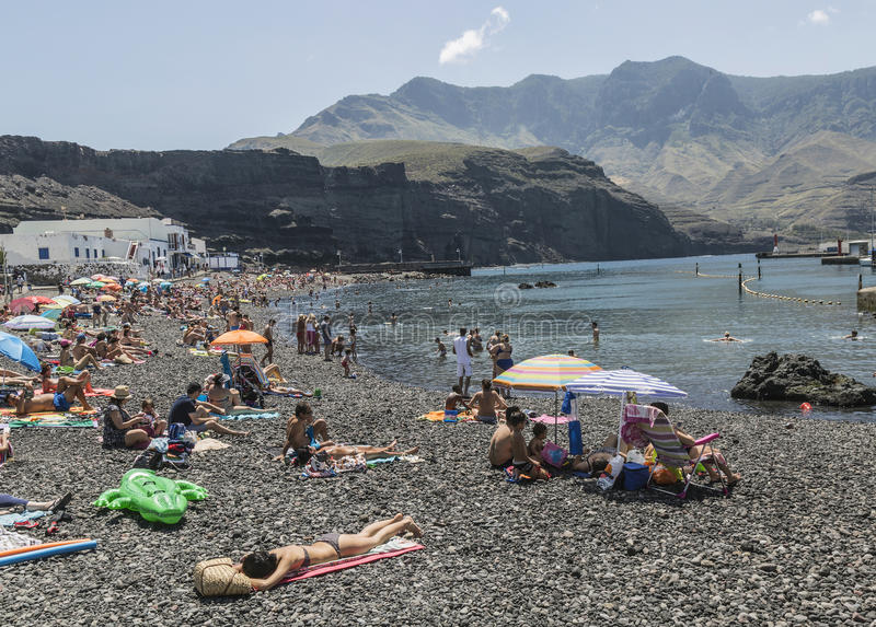 Tourists on pebbly beach at Puerto de las Nieves, on Gran Canaria. royalty free stock image