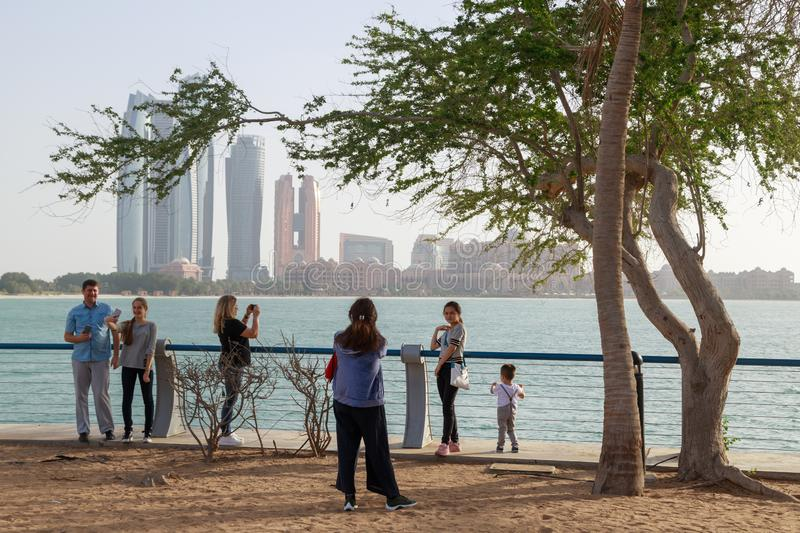 Tourists are photographed against the backdrop of beautiful high-rise buildings on the shore. ABU DHABI, UAE, JANUARY 10, 2019: Tourists are photographed against stock image