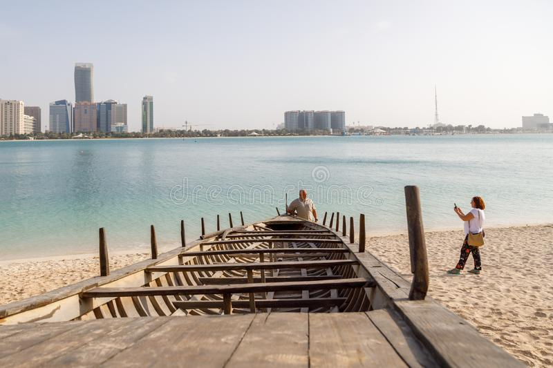 Tourists are photographed against the backdrop of a turquoise bay near an ancient traditional wooden boat in the Emirates Heritage stock images