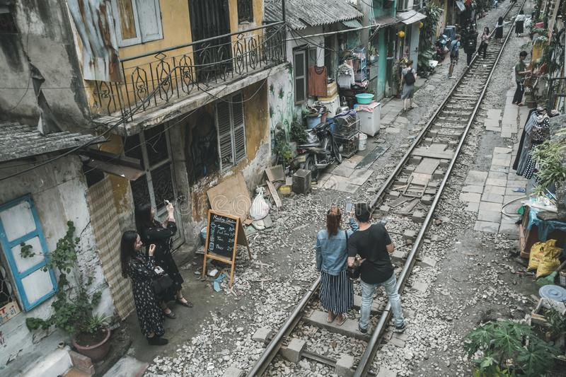 Tourists are photographed on the railway waiting for the train among the old houses of the poor quarter. Hanoi. Vietnam. 13 January 2019 stock photography