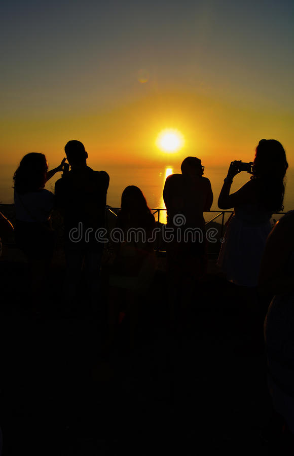 Tourists photographing sunset. Silhouettes of people at viewpoint on the top of the hill, watching and photographing sunset over the sea stock photography