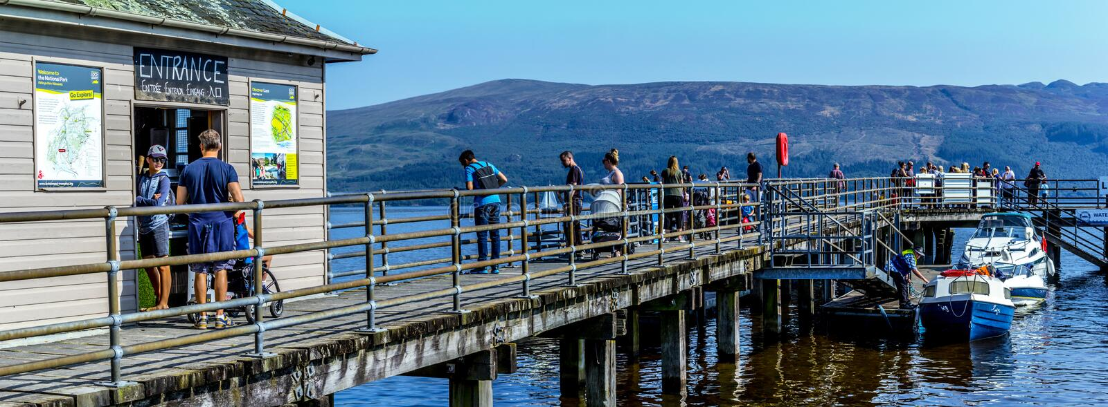 Tourists on the pier in Luss at Loch Lomond, Scotland, 25 August 2019. People relaxing and having fun during one of the hot days. Tourists on the pier in Luss at royalty free stock images