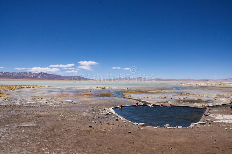 Tourists at the Polques hot springs in the Chalviri desert on the Salar de Uyuni tour Bolivia. Tourists at the Polques hot springs. Chalviri desert on the Salar royalty free stock image
