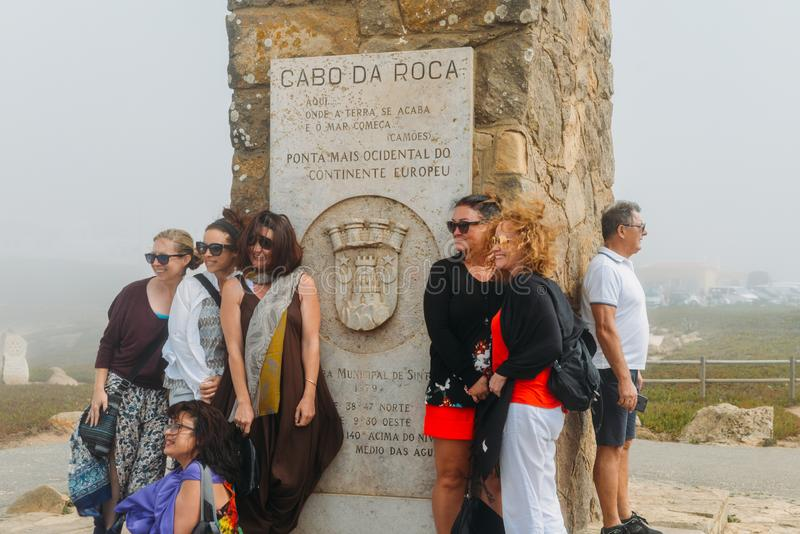 Tourists pose for a picture next to the monument declaring Cabo da Roca as the most western point of continental Europe. Cabo da Roca, Portugal - Sept 23, 2018 royalty free stock images