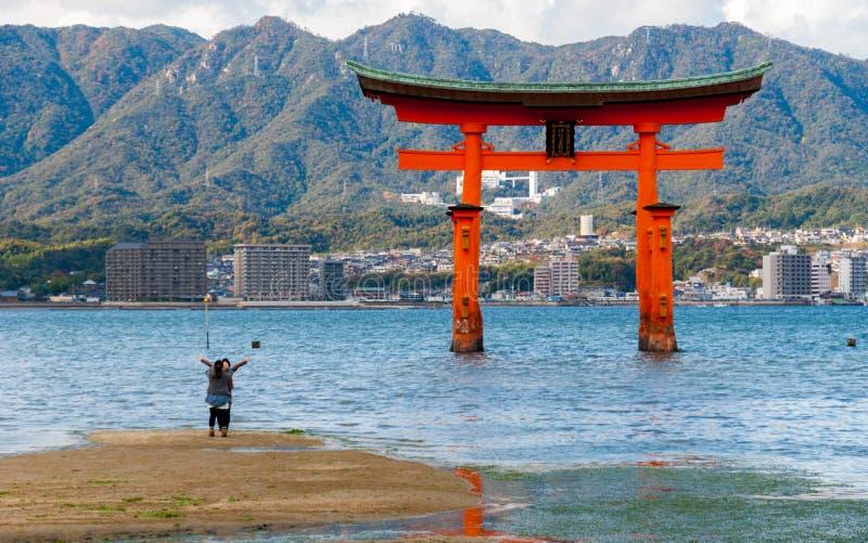 Tourists posing for photos in front of the O-torii gate on Miyajima (Itsukushima). Miyajima, Japan - November 15, 2010: Tourist posing for a photo in front of royalty free stock photos