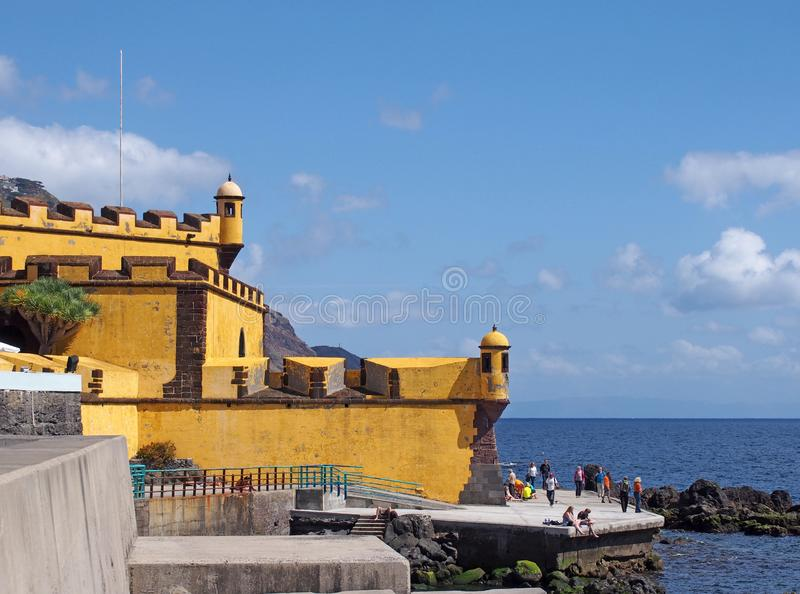 tourists relax by the sea outside the yellow fort in funchal madeira in bright sunshine royalty free stock image
