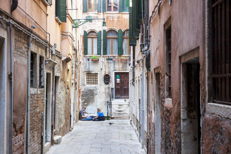 Tourists relaxing in a narrow street - Venice, Italy stock photos