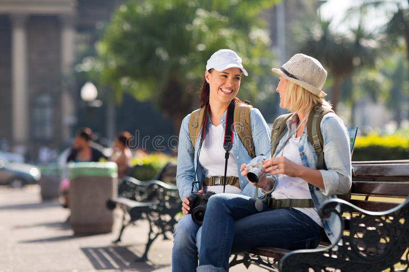 Tourists relaxing tour. Beautiful female tourists relaxing on bench during their tour in the city royalty free stock photos