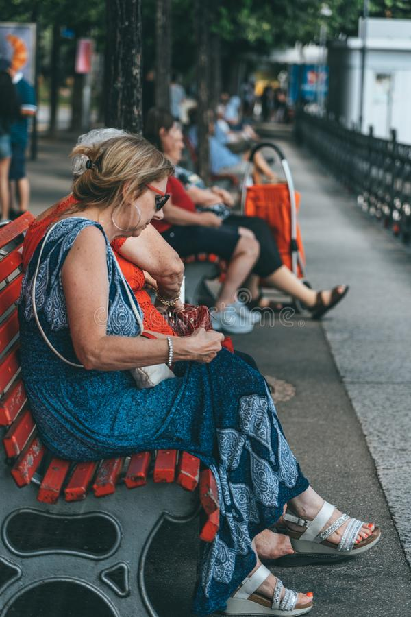 Lugano, Switzerland - August4, 2019: Tourists rest on red bench facing Lugano Lake in summer time stock image