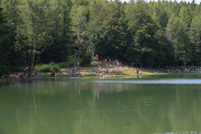 Tourists resting mear Ninfa lake on slope of Monte Cimone mountain, Emilia Romagna province, Italy royalty free stock image