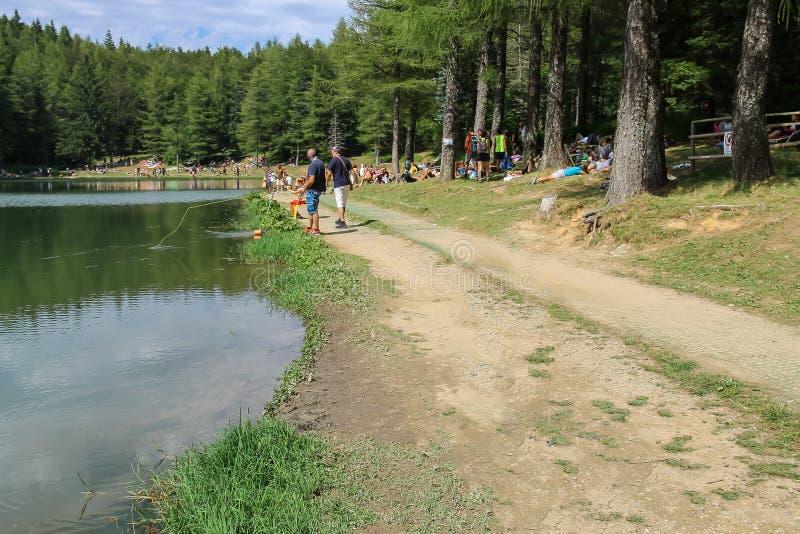 Tourists resting mear Ninfa lake on slope of Monte Cimone mountain, Emilia Romagna province, Italy stock photography