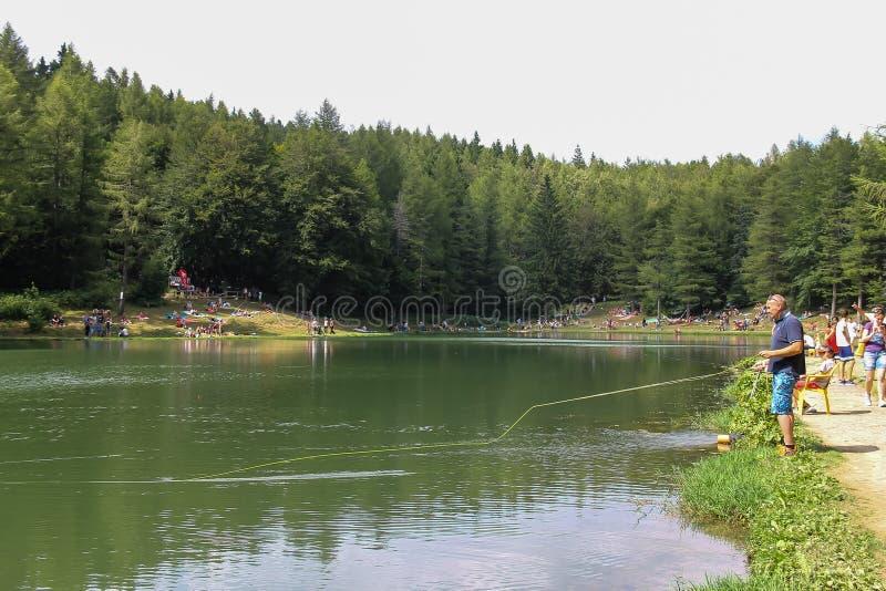 Tourists resting mear Ninfa lake on slope of Monte Cimone mountain, Emilia Romagna province, Italy stock images