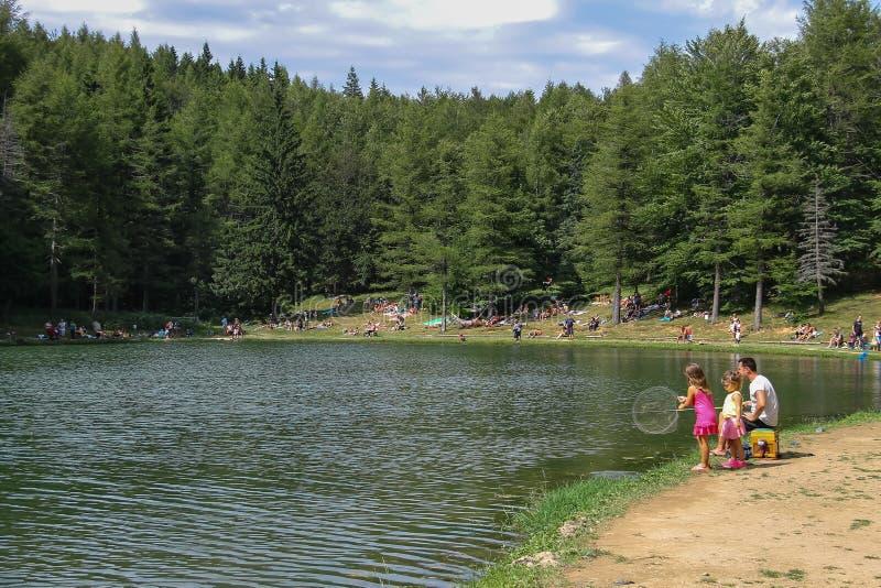 Tourists resting mear Ninfa lake on slope of Monte Cimone mountain, Emilia Romagna province, Italy royalty free stock photography