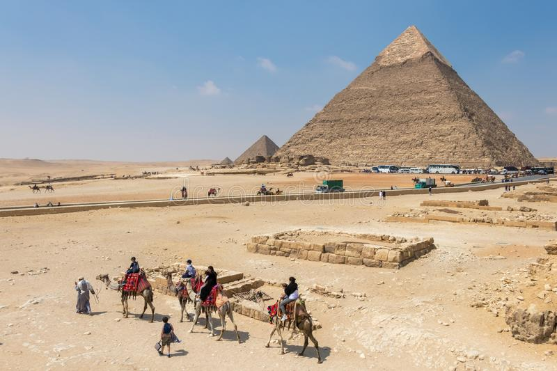 Tourists ride on camels guided by a local man at Giza in front of Pyramids, Egypt royalty free stock image