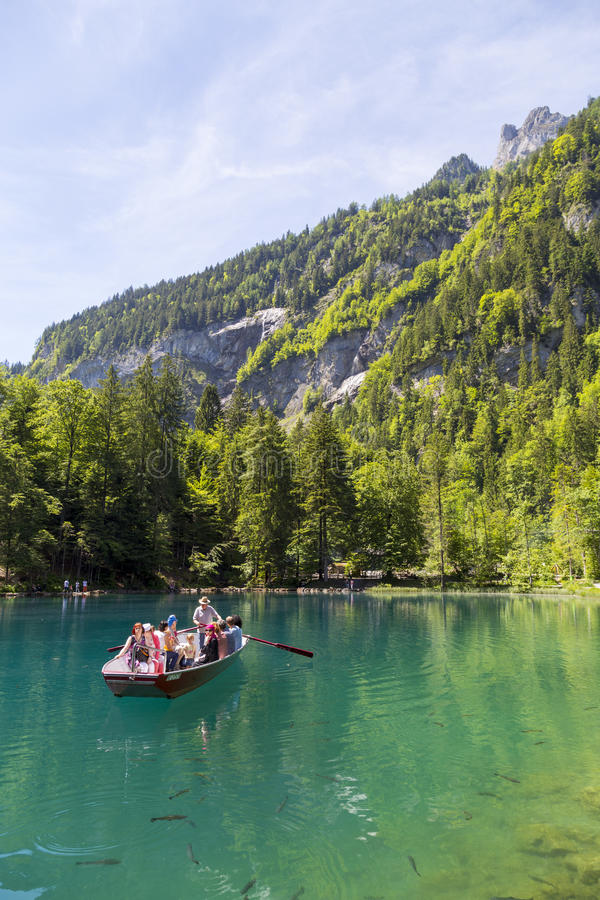 Tourists riding in boat at Blausee or Blue Lake nature park in summer, Kandersteg, Switzerland royalty free stock photography