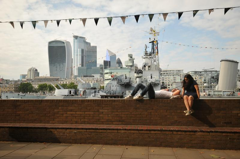 Tourists on river Thames , in front of the royal navy ship HMS Belfast. HMS Belfast is a Town-class light cruiser that was built for the Royal Navy. She is now royalty free stock photos