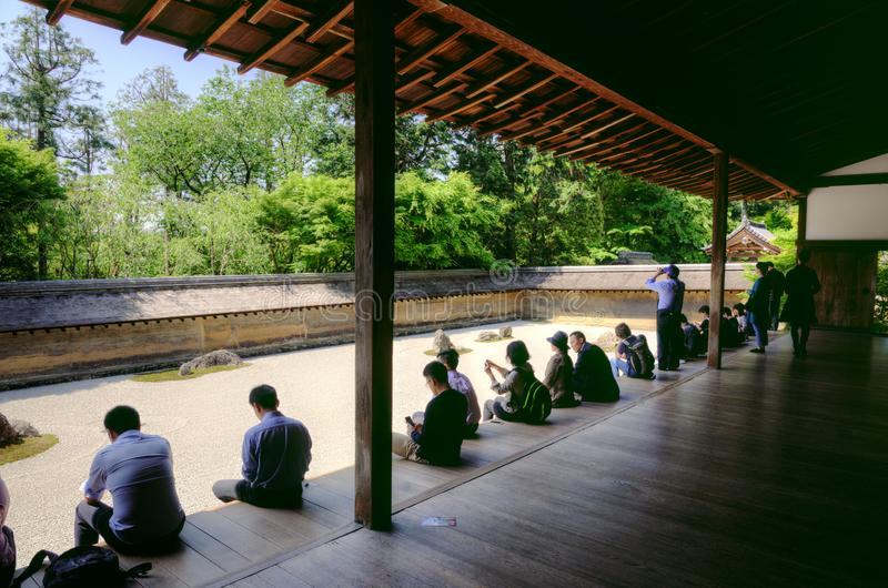 Tourists in Ryoanji zen temple, Kyoto, Japan. People sitting, taking pictures and meditating in front of a dry zen garden at Ryoanji buddhist temple, Kyoto city stock photos
