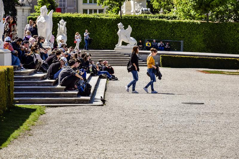 Tourists schoolchildren and students are sitting on the steps near the Belvedere Palace in Vienna. Vacations, holidays, weekends stock photo