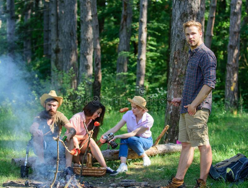 Tourists sharing thoughts about hike sit on log. Company having hike picnic nature background. Summer tradition. Picnic. With friends in forest near bonfire stock image