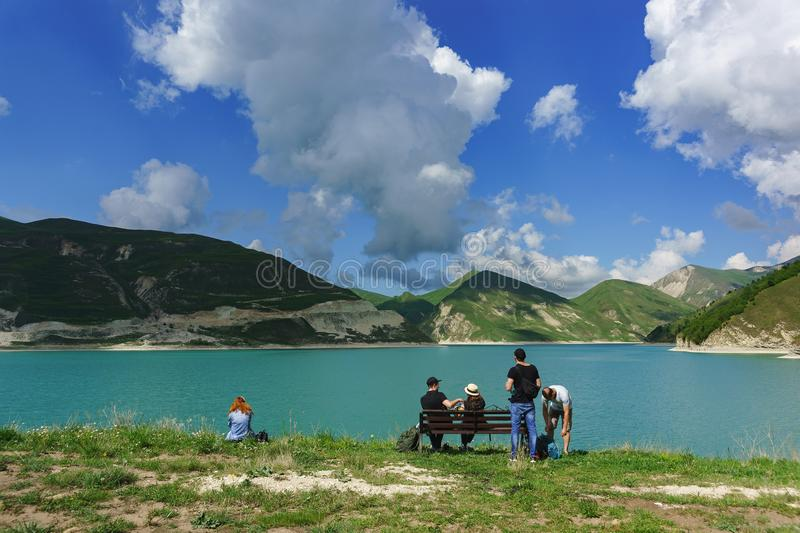 Tourists sit on a bench on the shore of lake Kezenoi am. Green grass on the mountain slopes in early summer stock photo