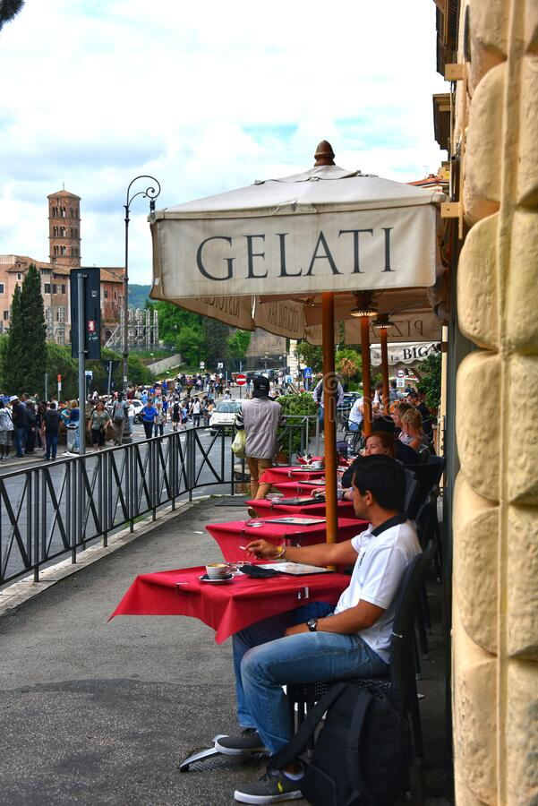 Tourists sit at outdoors tables in Rome, Italy royalty free stock image