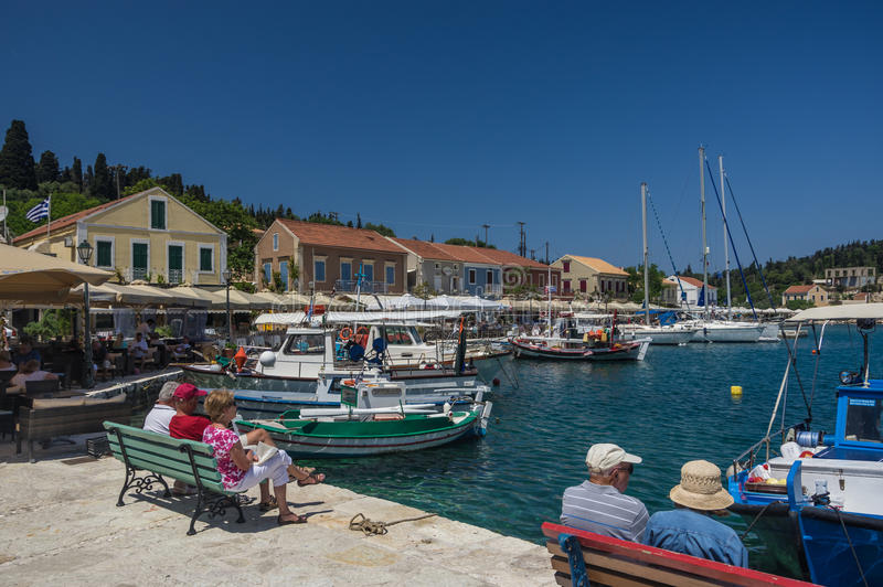 Tourists sit and relax amongst the restaurant, taverners and yacht boats in Fiskardo port royalty free stock photo