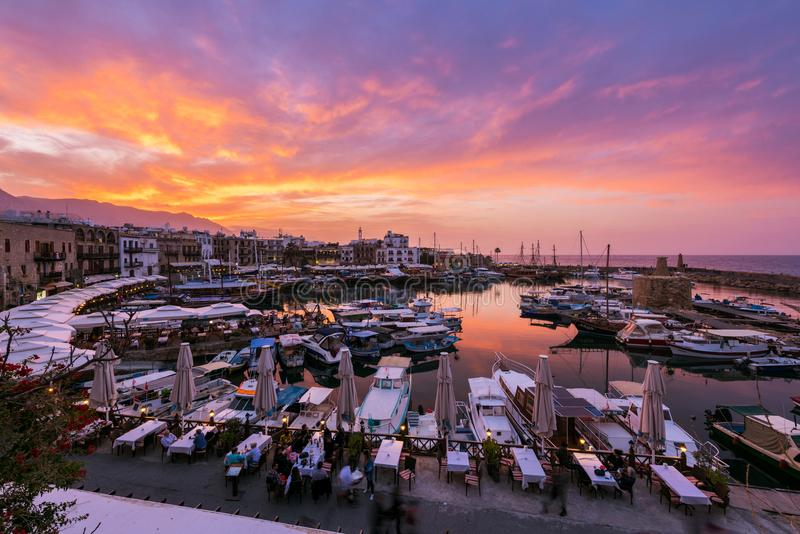 Tourists sitting at the outdoors cafes and enjoying amazing sunset and beautiful view of Kyrenia touristic harbor royalty free stock photography