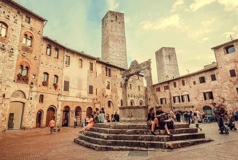 Tourists sitting on a square with historical brick towers of italian town royalty free stock image