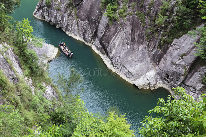 Tourists on the small boat, driving in the valley between the streams. Calm winding streams, steep slopes, diversity of vegetation royalty free stock image