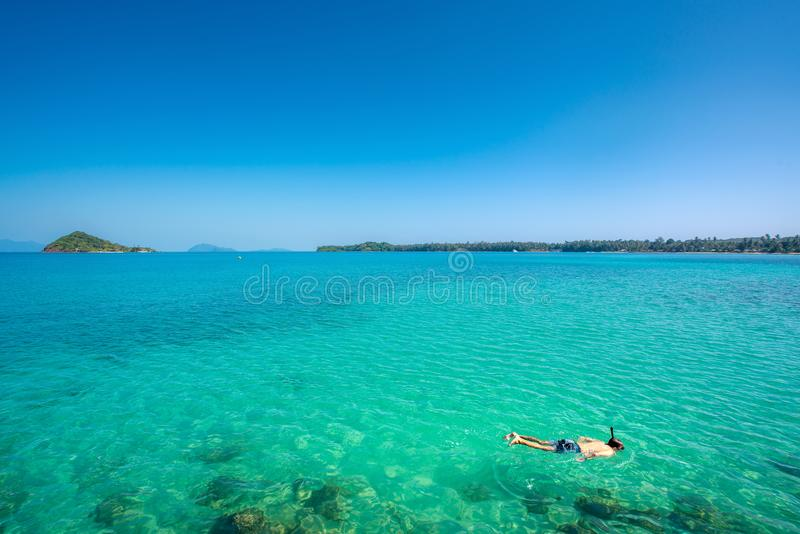 Tourists snorkel in crystal turquoise water near tropical resort in Phuket, Thailand. Summer, Vacation, Travel and Holiday concept.  royalty free stock photography