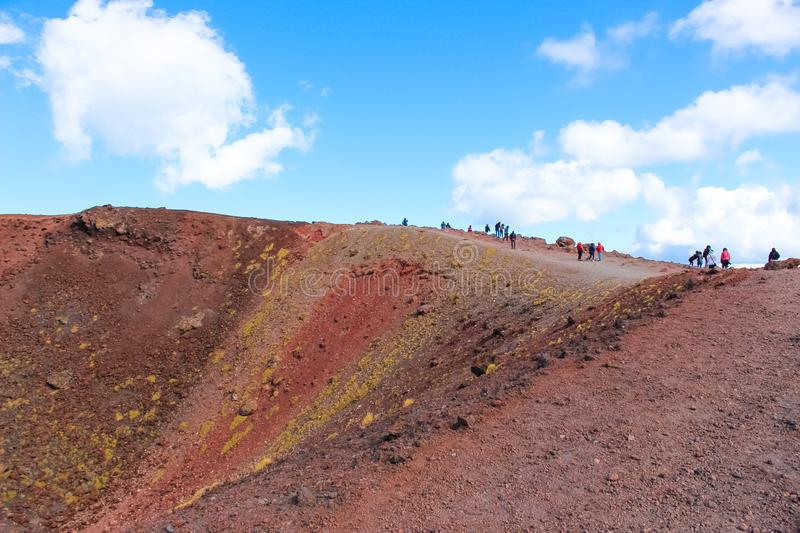 Tourists standing on the edge of Silvestri craters on Mount Etna in Italian Sicily. The colorful volcanic landscape is popular stock photo