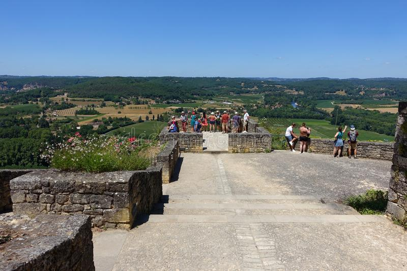 Tourists standing on a viewing platform overlooking the Dordogne from the town of Domme in France. Domme, France 15 July 2019: Tourists standing on a viewing royalty free stock images