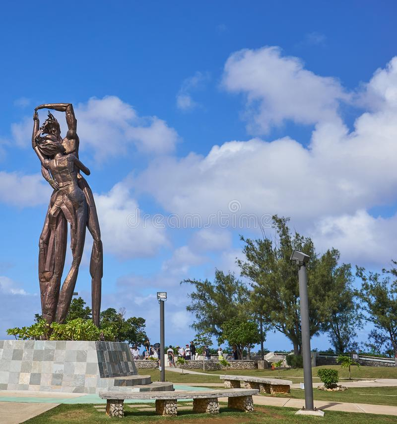 Tourists and the statue of two lovers hugging each other at Lover`s Point at Guam, USA stock photo