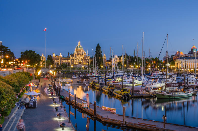 Tourists strolling the causeway of Victoria's Inner Harbor at night stock images