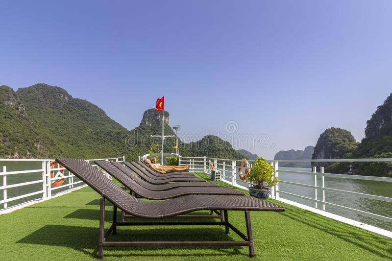 Tourists sunbathing in boat rooftop at Ha Long Bay Descending Dragon Bay popular tourist destination in Asia. stock image