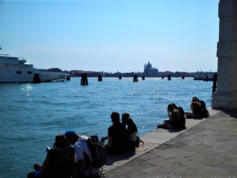 Tourists in Venice city, Italy. Sunny day, travel, bright sea and boats royalty free stock photography