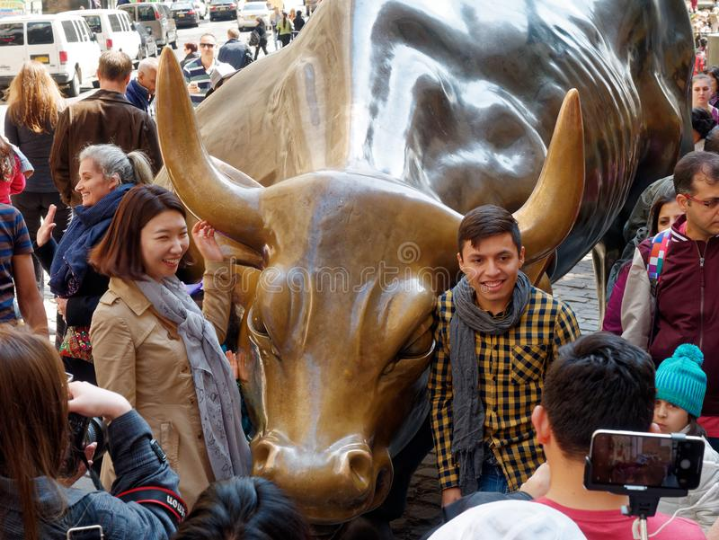 Tourists surrounding Wall Street Charging Bull Statue in Manhattan Financial District stock photography