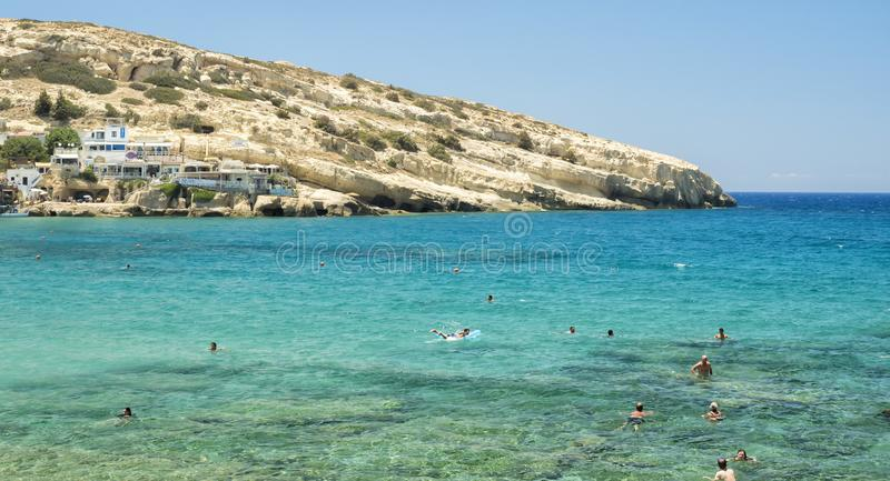 Tourists swimming at Matala beach, Crete Island, Greece - 22 June 2018.  royalty free stock image