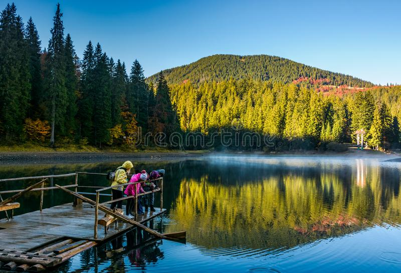 Tourists on Synevyr lake feed fish from the raft stock photography