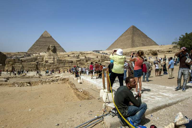 Tourists take photographs of the magnificent view at Giza in Cairo, Egypt. Tourists take photographs of the magnificent view showing the Sphinx, the Pyramid of stock photos