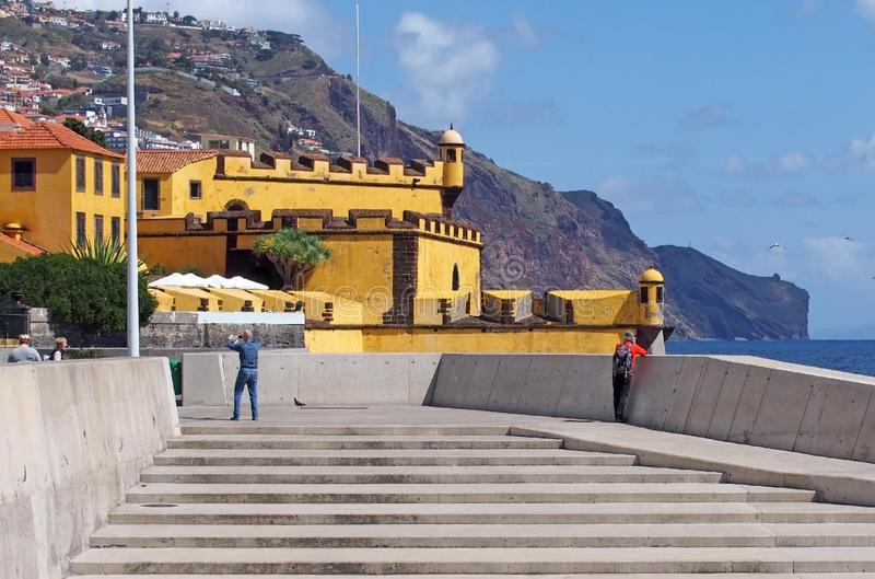 tourists take photos and look at the view by the sea outside the yellow fort in funchal madeira in bright sunshine stock photo