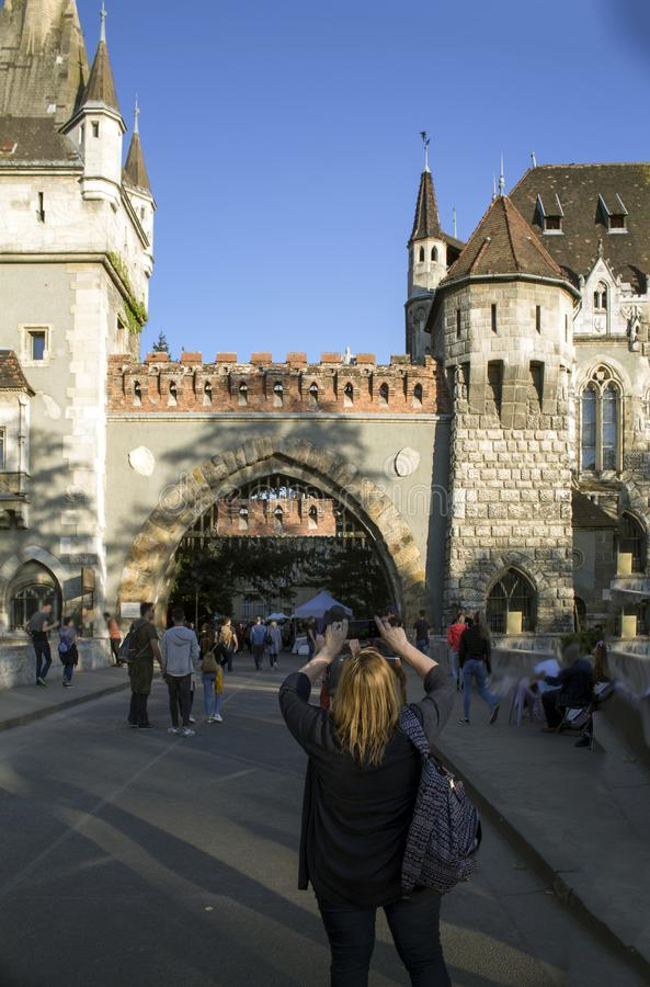 Tourists take photos of Vajdahunyad Castle in Hungary in Budapest. stock photos